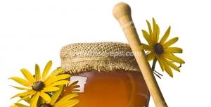 عکس با کیفیت شیشه عسل در کنار گل های بابونه و قاشق چوبی مخصوص عسل