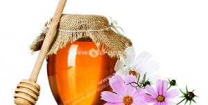عکس با کیفیت شیشه عسل با قاشق مخصوص عسل در کنار گل های سوسنی رنگ آستر