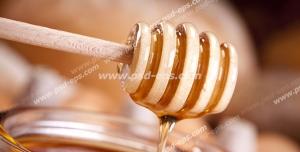 عکس با کیفیت برداشتن عسل از درون شیشه آن با قاشق مخصوص عسل از روی میز صبحانه