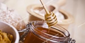 عکس با کیفیت شیشه عسل بر روی میز و برداشتن عسل از درون آن با قاشق مخصوص عسل
