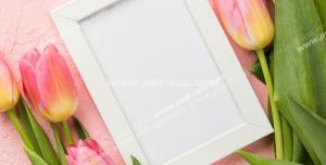 قاب عکس سفید در میان گل های لاله وحشی زرد و صورتی رنگ بر روی زمینه صورتی
