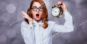 عکس با کیفیت تبلیغاتی خانمی که ساعت زنگدار به دست دارد و چهره ای متعجب و هراسان دارد