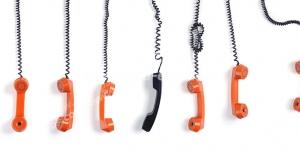 عکس با کیفیت گوشی تلفن مشکی در میان گوشی های نارنجی رنگ آویزان از بالای تصویر