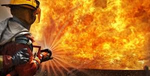 عکس با کیفیت تبلیغاتی آتش نشان در حال خاموش کردن آتش