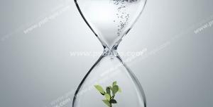 عکس با کیفیت تبلیغاتی ساعت شنی که داخل آن یک گیاه در آب است و حباب ها در آن به سمت بالا می روند
