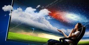 عکس با کیفیت تبلیغاتی خانمی که با کنترل در دست مقابل یک نمایشگر خیلی بزرگ نشسته است بالای سر او آسمان و ابر و کهکشان راه شیری است که از صفحه نمایشگر خارج شده است
