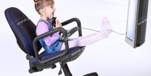 عکس با کیفیت تبلیغاتی دختر بچه کوچک در حال انجام باز ی کامپیوتری مقابل تلویزیون نشسته روی صندلی چرخدار متحرک در حالی ک صندلی کج شده و موهای دختر بالا رفته