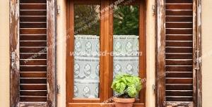 عکس با کیفیت تبلیغاتی پنجره چوبی زیبا با حفاظ چوبی قهوه ای سوخته و یک گلدان سفالی زیبا جلوی آن