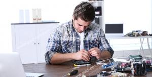 عکس با کیفیت تبلیغاتی مرد در حال تعمیر برد لپ تاپ روی میز با ابزار تعمیر و فن و پیچ گوشتی و لپ تاپ و کمد