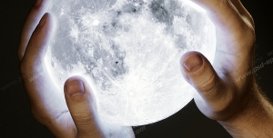 عکس با کیفیت تبلیغاتی کره ماه در دستان مرد