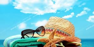 عکس با کیفیت تبلیغاتی کلاه و عینک بر روی حوله لب ساحل