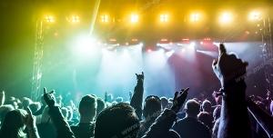 عکس با کیفیت تبلیغاتی مردم در کنسرت در حال شادی زیر نور های رنگارنگ