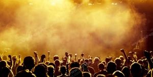 عکس با کیفیت تبلیغاتی مردم در کنسرت در حال شادی زیر نور و دود