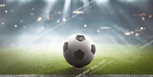 عکس با کیفیت تبلیغاتی توپ فوتبال در وسط زمین فوتبال زیر نور افکن ها