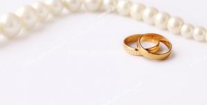 عکس با کیفیت تبلیغاتی دو حلقه طلا در کنار ریسه مروارید زیبا