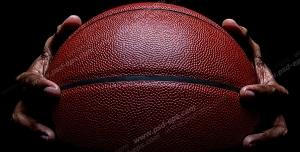 عکس با کیفیت تبلیغاتی توپ بسکتبال بین دو دست در تاریکی