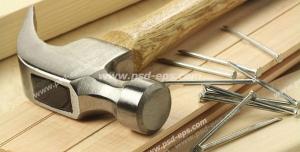 عکس با کیفیت تبلیغاتی چکش و چند میخ که روی سطح چوبی قرار دارند