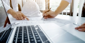 عکس با کیفیت تبلیغاتی مهندسان در حال برسی نقشه و لپ تاپ و کلاه ایمنی بر روی میز