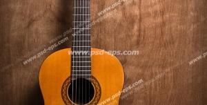 عکس با کیفیت تبلیغاتی گیتار کلاسیک با بدنه ی نارنجی بر روی میز چوبی