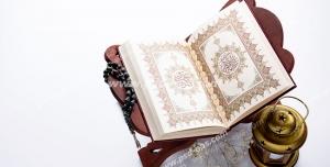 عکس با کیفیت تبلیغاتی قرآن بر روی رحل و فانوس کوچک در کنارش در زمینه سفید