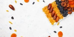 عکس با کیفیت تبلیغاتی خشکبار در ظرف چیده شده و آلو ها و خرمای خشک به شکل دایره