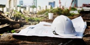 عکس با کیفیت تبلیغاتی کلاه ایمنی سفید بر روی نقشه های ساختمان و خانه ها در حال ساخت در نمای دور