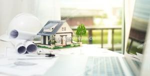 عکس با کیفیت تبلیغاتی لپ تاپ در کنار ماکت خانه کوچک و نقشه های لول شده ی ساختمان