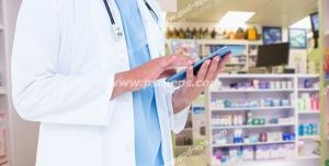 عکس با کیفیت تبلیغاتی پزشک در حال کار کردن با تبلت و قفسه های دارو در پشت سرش
