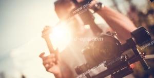 عکس با کیفیت تبلیغاتی مرد در حال فیلم برداری با دوربین حرفه ای و تابیده شدن نور خورشید از پشت سر فیلم بردار
