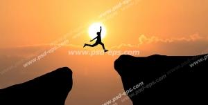 عکس با کیفیت تبلیغاتی مرد در حال پرش از قله ای به قله ای دیگر در غروب آفتاب