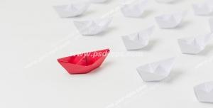عکس با کیفیت تبلیغاتی قایق های کاغذی سفید پشت سر یک قایق کاغذی قرمز