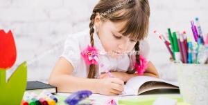 عکس با کیفیت تبلیغاتی دختر بچه زیبا با موهای بافته شده نشسته پشت میز در حال رنگ آمیزی و نقاشی