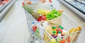 عکس با کیفیت تبلیغاتی سبد چرخدار فروشگاه در دست زن و سبد پر شده از سبزیجات و میوه و مواد غذایی