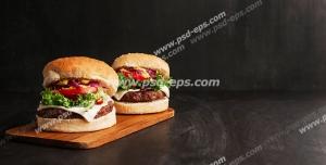 عکس با کیفیت تبلیغاتی دو همبرگر لذیذ بر روی تخته چوبی و بک گراند مشکی
