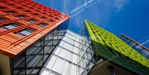 عکس با کیفیت تبلیغاتی ساختمان ها با نمای سبز و نارنجی در زیر سقف آسمان آبی