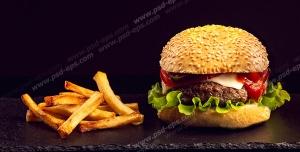 عکس با کیفیت تبلیغاتی همبرگرد لذیذ در کنار سیب زمینی های سرخ شده در بک گراند مشکی