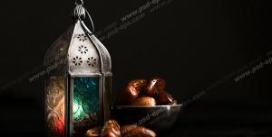 عکس با کیفیت تبلیغاتی چراغ کوچک در کنار ظرف خرما در بک گراند مشکی