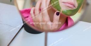 عکس با کیفیت تبلیغاتی تصویر زن در آینه و در حال گذاشتن ماسک سبز بر روی صورت