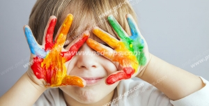 عکس با کیفیت تبلیغاتی کودک لبخند بر لب و دو دست رنگی جلوی صورت گرفته شده است