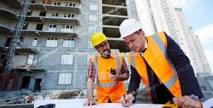 عکس با کیفیت تبلیغاتی مهندس ناظر در حال برسی نقشه در کنار یکی از کارگران ساختمان و ساختمان های بزرگ و مرتفع در پشت سرشان