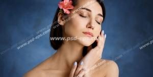 عکس با کیفیت تبلیغاتی زن با چشمای بسته شده و گل زیبا بر روی موهای کوتاه او و بک گراند سرمه ای